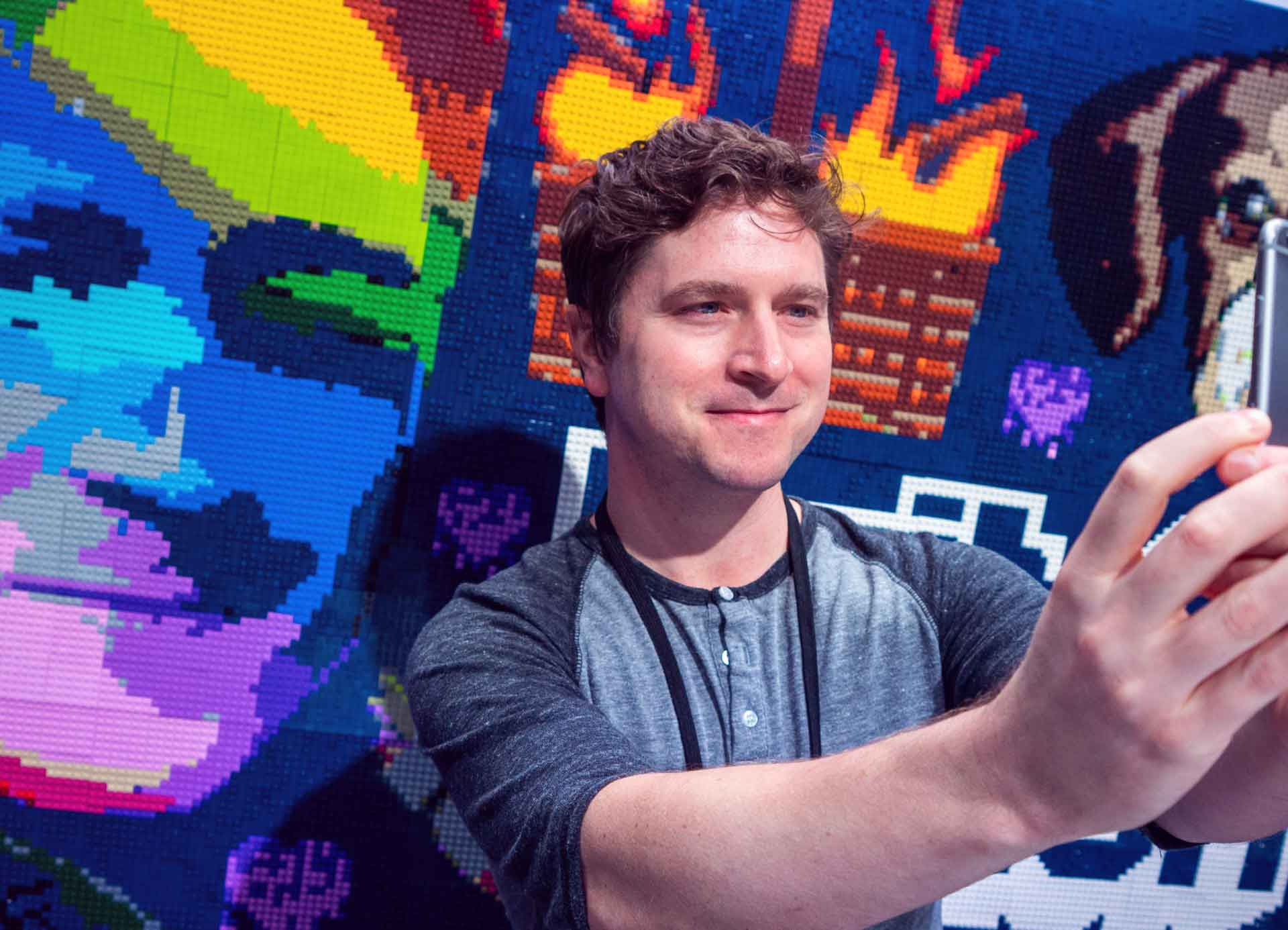 The real life Kappa poses in front of a mural of his popular emote.